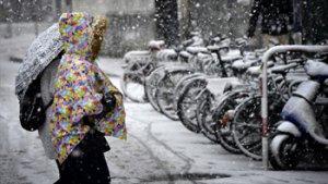 iemand met bonte mantel steekt straat over in de sneeuw