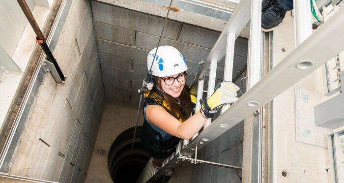 Meisje met veiligheidshelm klimt naar beneden via trapladder