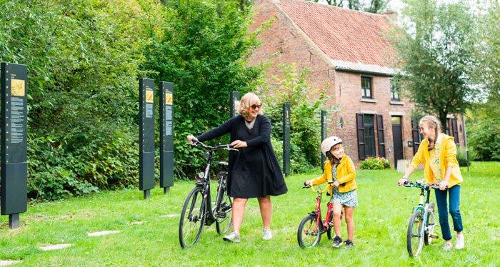 Vrouw met 2 kinderen met fiets aan hun hand