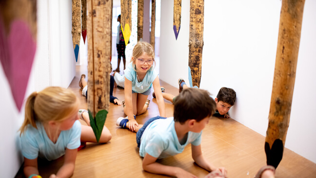 Kinderen kruipen door en 'bos' met kleurrijke, hangende reuzenpotloden