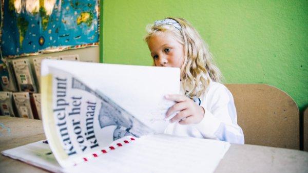 Meisje kijk in bundel met krantenknipsels