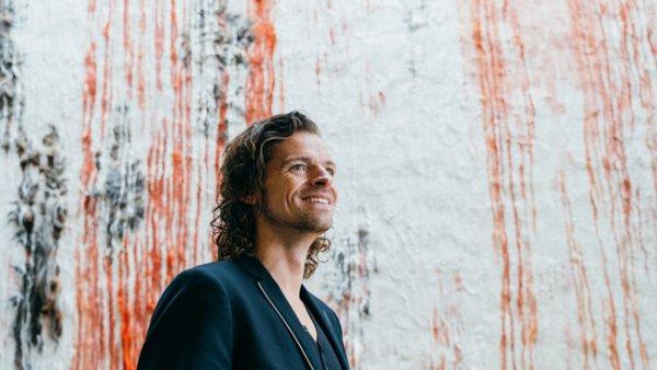 Portret van Maurice De Greef voor muur met rode verf