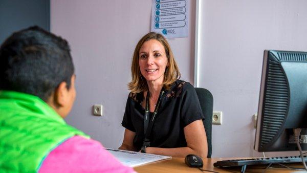 Leerlingen op de bureau in gesprek met Pedagogisch coördinator Ellen