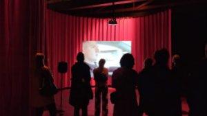 mensen kijken naar scherm in theaterzaal