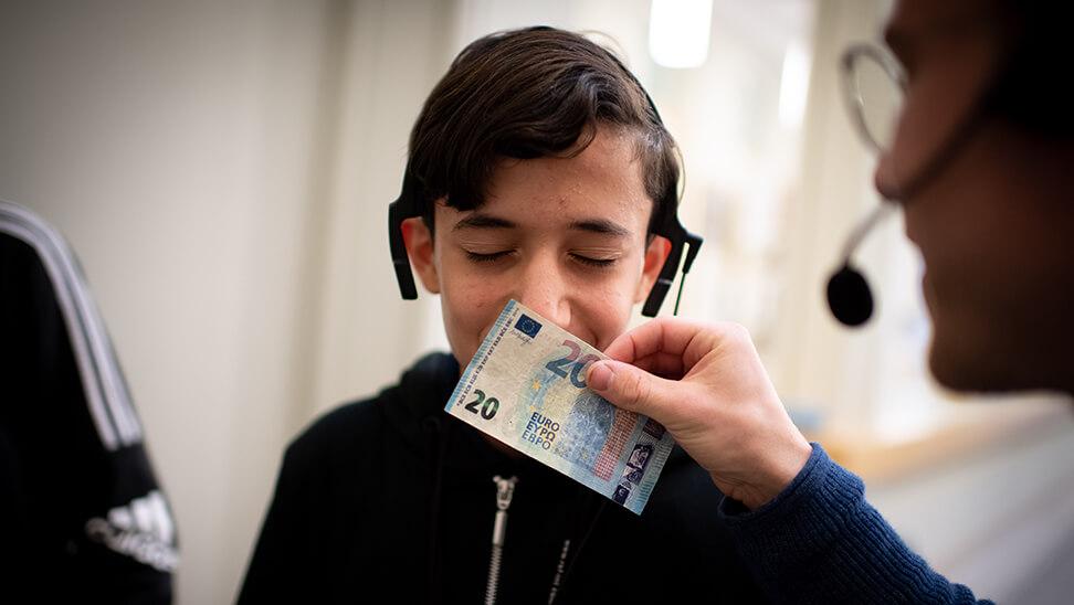 leerling mohamed ruikt aan een briefje van  20 euro