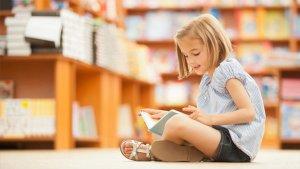 Meisje zit voor boekenrek en leest boek