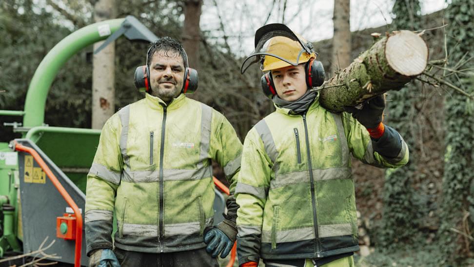Florian en begeleider Kris poseren met een boomstronk.