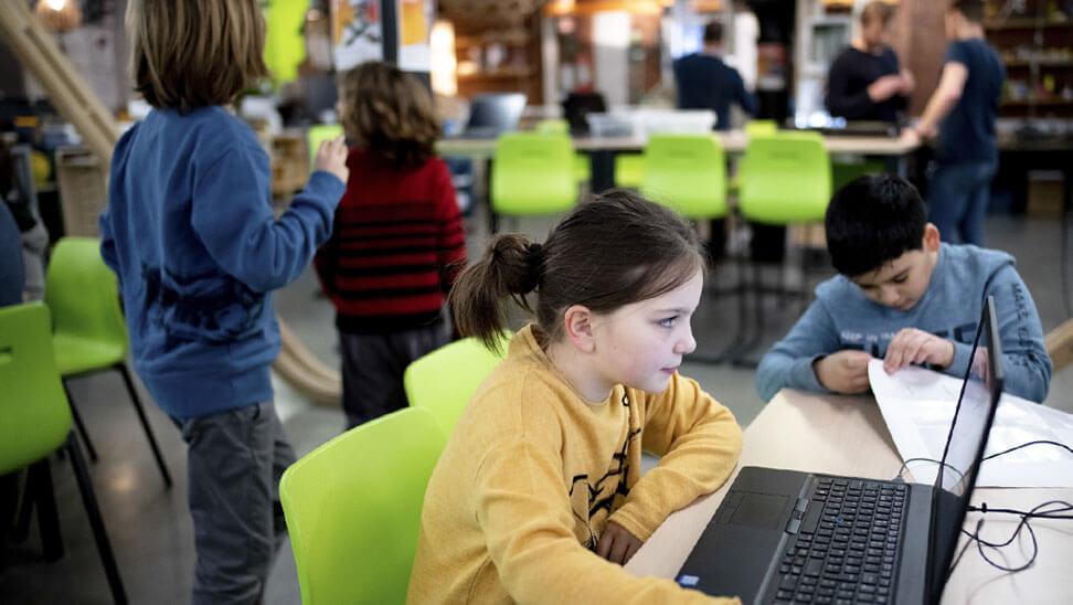 De leerlingen werken in groepjes achter laptops.