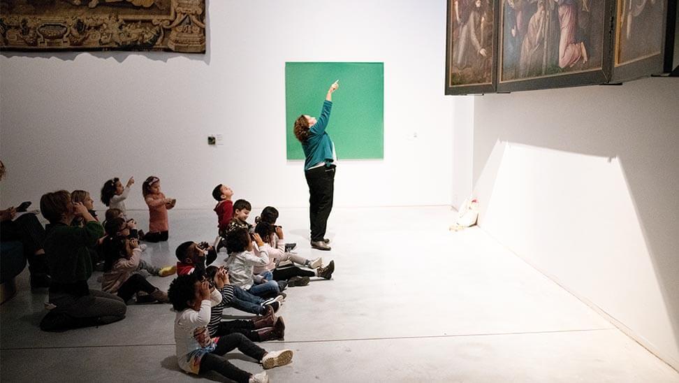 Kinderen kijken door een verrekijkertje naar een schilderij in M-Museum Leuven