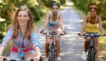 Drie meisjes fietsen op een weg omringd door groen