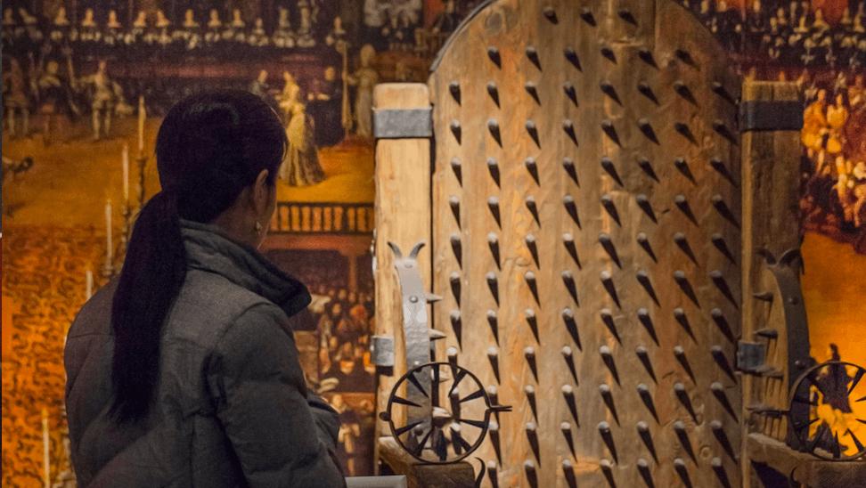 bezoeker aan het torture museum naast een foltertuig