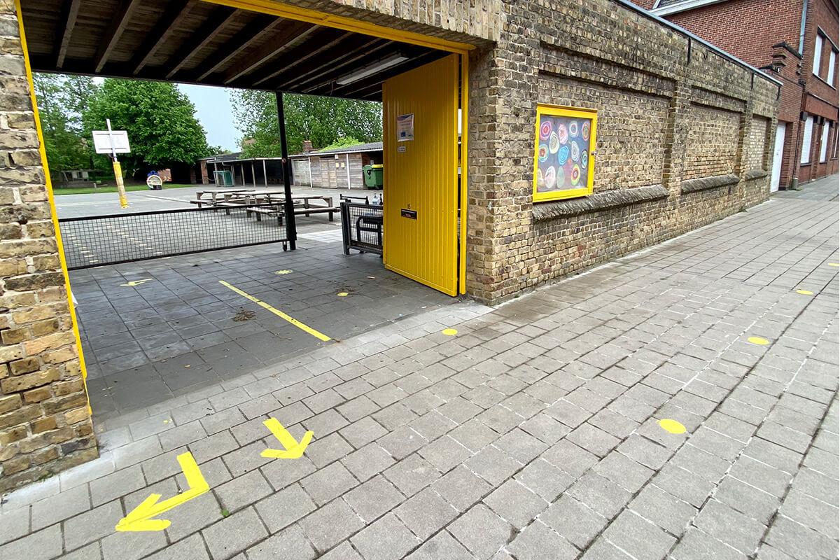 Wachtstippen en looproutes aan de ingang. Zo kunnen ouders veilig hun kind brengen en halen.