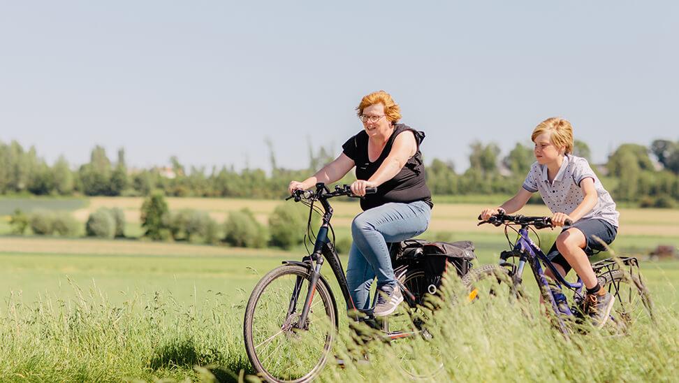 Ondersteuner Maai Quartier fietst met een leerling