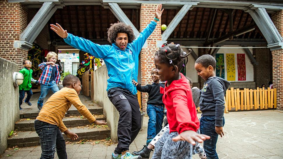 Kinderen spelen met animator van buurtwerk 'tLampeke