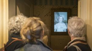 bezoekers kijken naar video over koningin Louise-Marie