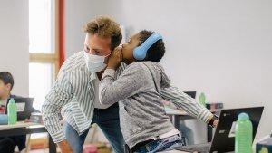 leerling fluistert in het oor van leraar Rens Gijsen