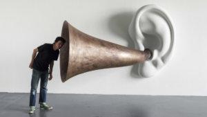 man luistert naar reuze antieke luidspreker