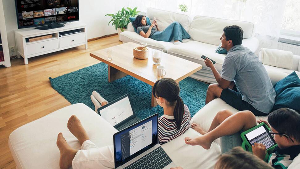Een familie samen in de woonkamer waarbij enkele familieleden 1Password op hun toestel gebruiken