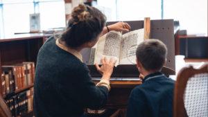 Vrouw toont middeleeuws boek aan kind