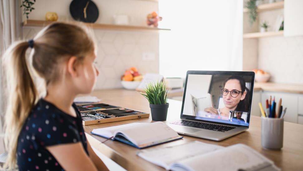 Meisje praat met leraar via computer