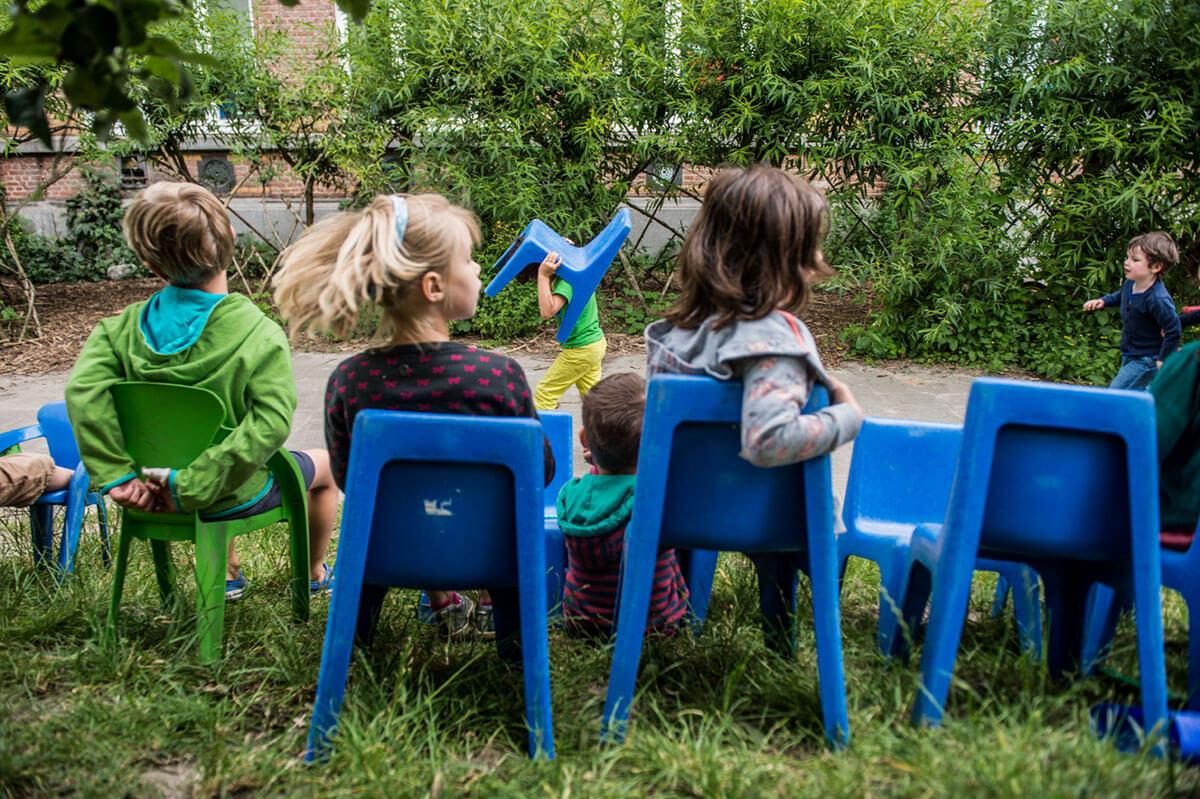 Kinderen zitten op blauwe stoeltjes