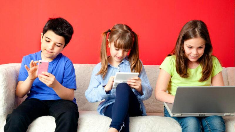 kinderen op een bank met laptop of smartphone