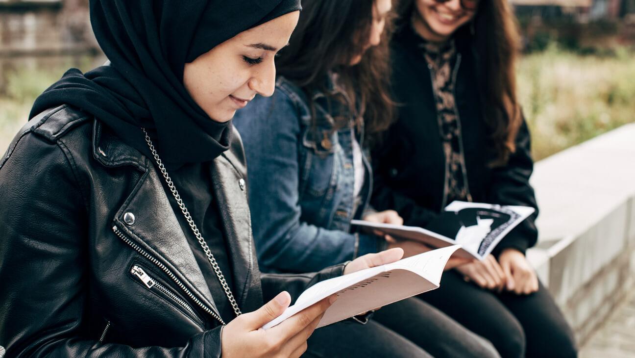 OKNA-leerling leest in handboek Overhaald