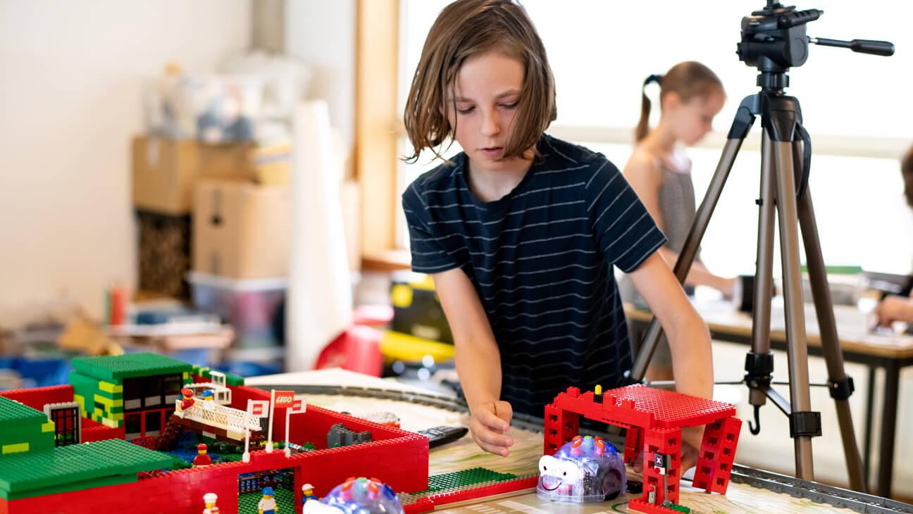Leerling plaatst robot in Lego-stad