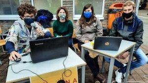 leerlingen op een laptop op de speelplaats