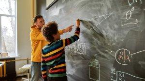 Leraar met leerling aan schoolbord