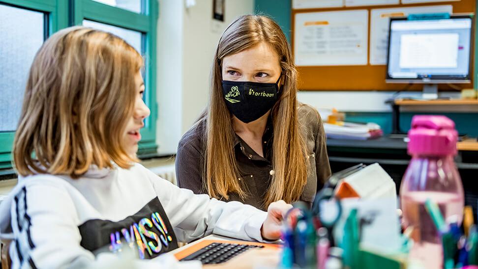 Kind werkt met leraar op tablet