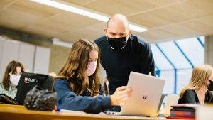 leraar Maarten De Vos in de klas met een leerling op haar laptop