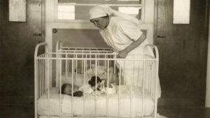 foto van een verpleegster bij een kind in een wieg