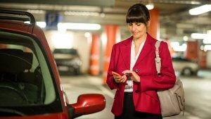 Vrouw met gsm in parkeergarage