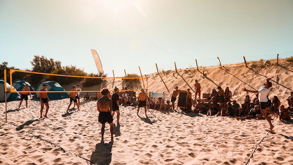 Jongeren spelen volleybal tijdens surfkamp