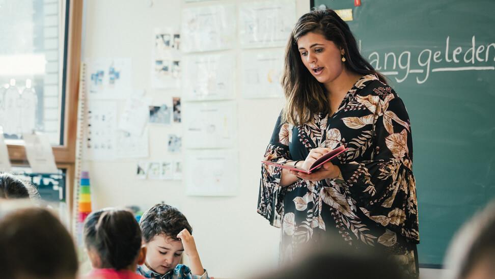 Kendra D'Hondt, leraar eerste leerjaar, leest voor uit een boek