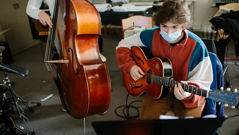 Jongen met een gitaar in de kunsthumaniora