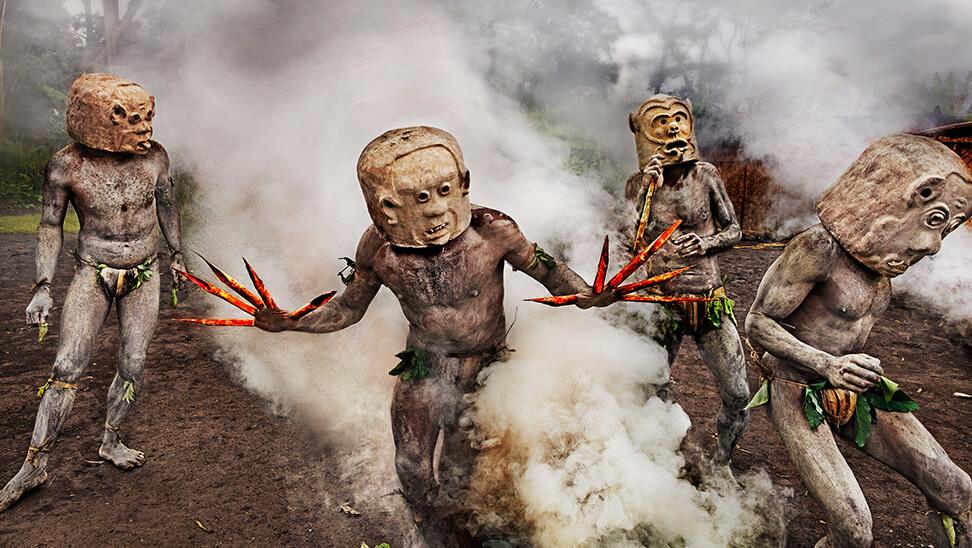 Tribesmen with their clay masks and bamboo garb emerge from smoke which symbolizes the heavens descending to the earth. Geremiyaka Village, Papua New Guinea, 2017