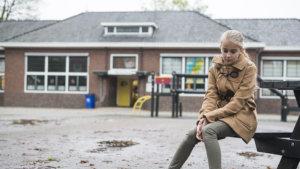Meisje buiten op een bank aan de school