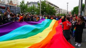 Foto van mensen bij een regenboogvlag tijdens een optocht