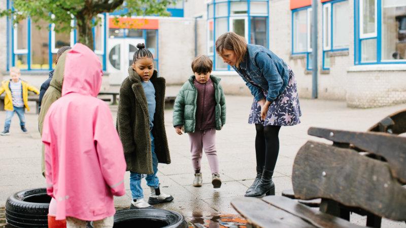 Directeur Eva Naaijkens met leerlingen op speelplaats