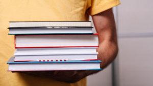 Leraar draagt handboeken