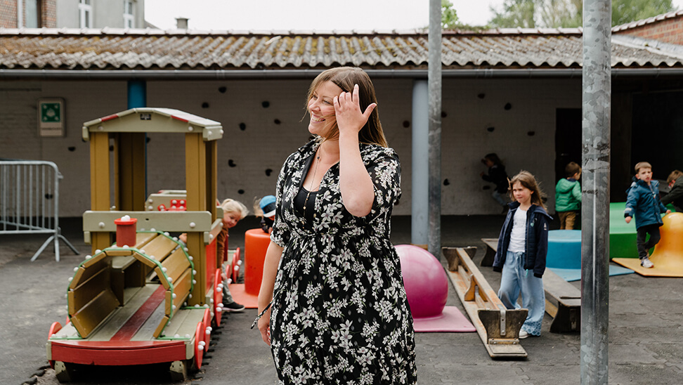 Leraar Corine met haar kleuters op de speelplaats