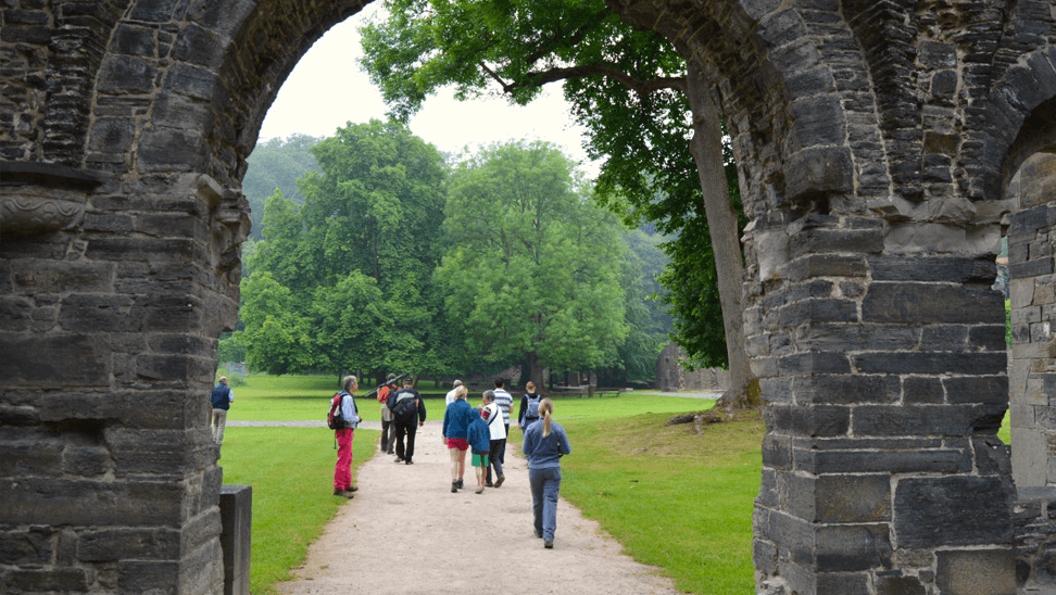 Wandelaars onder een boog van de Abdij van Villers